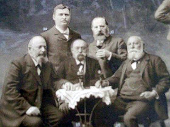 Fotocollage: Sigmund Hirsch (links am Tisch sitzend) in der Schützengesellschaft 1860 Weinheim. / Fotocollage mit Grauton-Malerei in Tempera als Hintergrund, 1904.